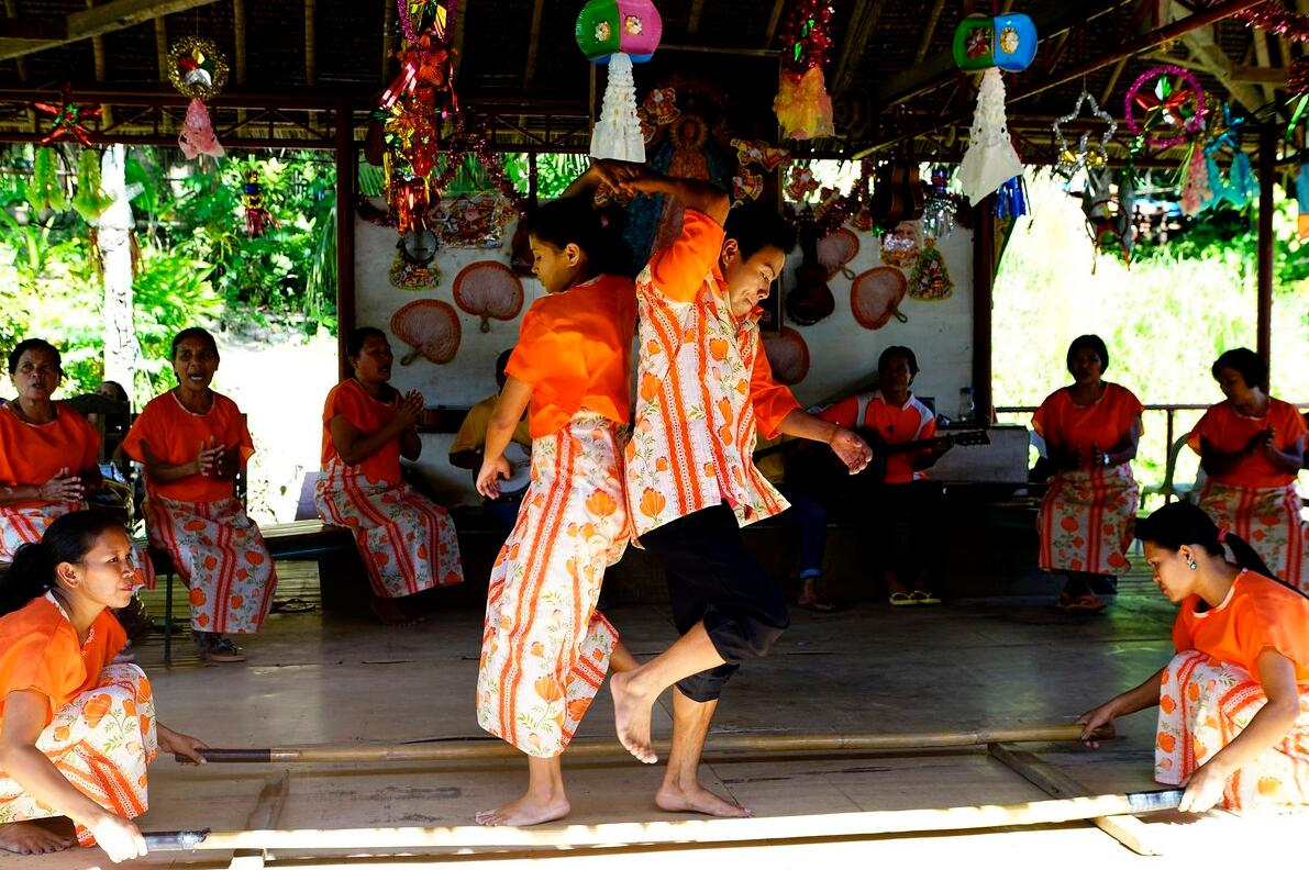 People dancing the Philippine national dance Tinikling