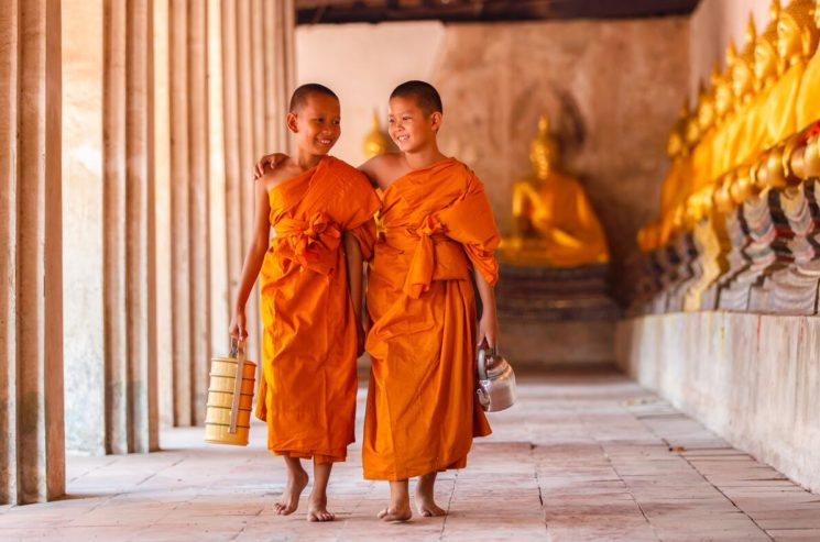 Two boys walking and talking in the old temple in Cambodia